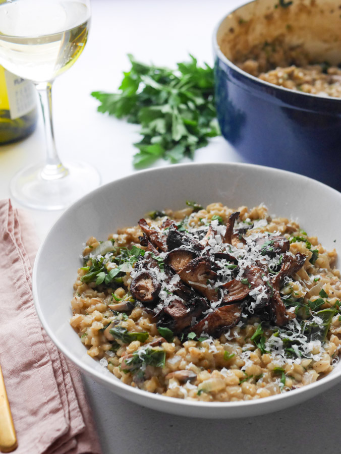 Mushroom pearl barley risotto in a white bowl, topped with crispy roasted mushrooms and garnished with chopped parsley and grated parmesan. Next to the bowl is a glass of white wine, and in the background is the cast iron pot in which the risotto was cooked sitting.