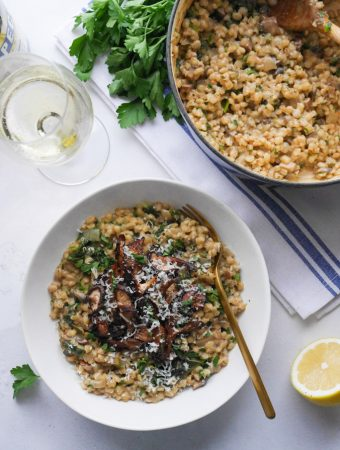 Mushroom pearl barley risotto in a white bowl, topped with crispy roasted mushrooms and garnished with chopped parsley and grated parmesan. Next to the bowl is a glass of white wine, a wedge of lemon and the blue cast iron pot that the pearl barley risotto was cooked in.