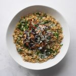 Mushroom pearl barley risotto in a white bowl, topped with crispy roasted mushrooms and garnished with chopped parsley and grated parmesan.