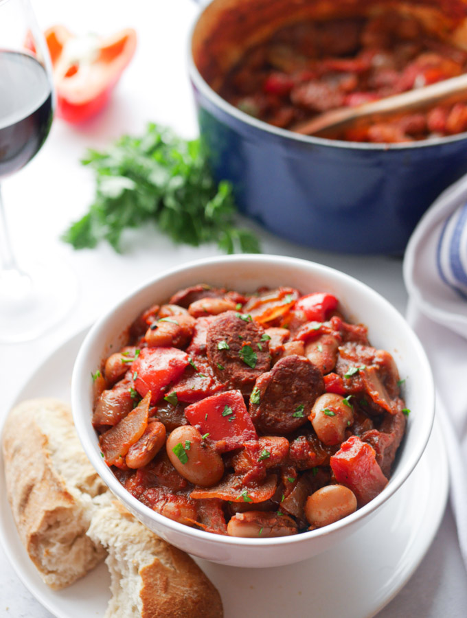 A bowl of chorizo stew with butterbeans. Next to the bowl is a bread roll. There is also a blue casserole pot with the remainder of the stew in.