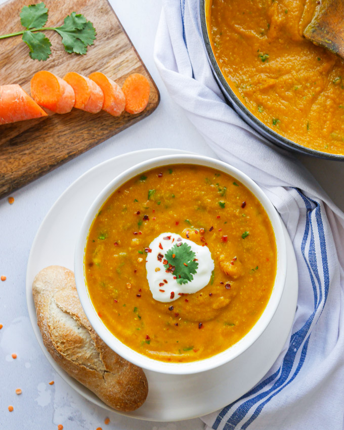Spicy carrot and lentil soup in a white bowl. The soup is garnished with fresh coriander, dried chillis and a dollop of vegan yogurt. Next to the bowl is a bread roll. There is a casserole pot filled with the soup next to the bowl and a chopping board with sliced carrot on it.