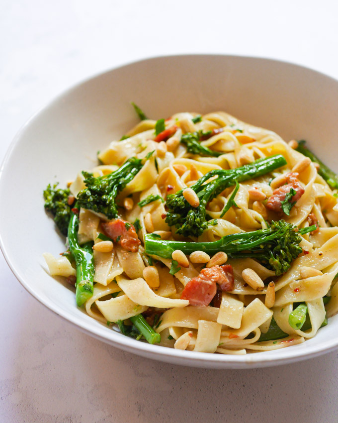 A white bowl of broccoli tagliatelle pasta, garnished with chopped parsley and pine nuts.
