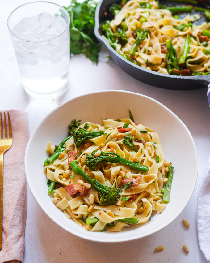 A bowl of tagliatelle pasta with broccoli and bacon, garnished with chopped parsley and toasted pine nuts. Behind the bowl is a cast iron skillet filled with more broccoli and bacon tagliatelle.