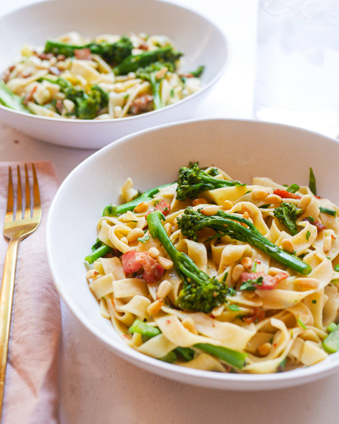 Two white bowls, both filled with tagliatelle pasta with broccoli and bacon. Next to one of the bowls is a pink napkin with a gold fork.