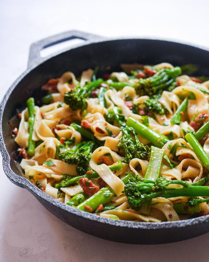 Tagliatelle Pasta with Broccoli and Bacon in a cast iron skillet.