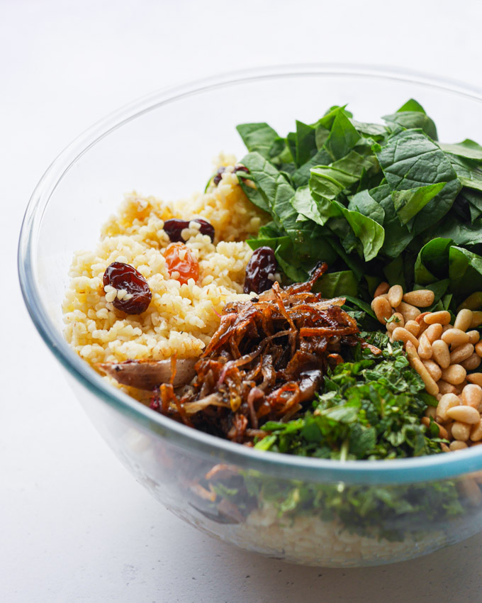 The ingredients for bulgur salad, including caramelised onions, spinach, pine nuts, bulgur wheat, herbs and raisins, in a clear glass bowl.