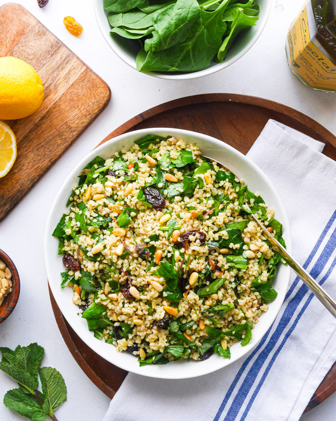 A bowl of bulgur salad with a serving spoon in it, sitting on a wooden tray. Next to the bulgur and spinach salad is a chopping board with a cut lemon on it, a small bowl of pine nuts and a bowl of fresh spinach leaves.