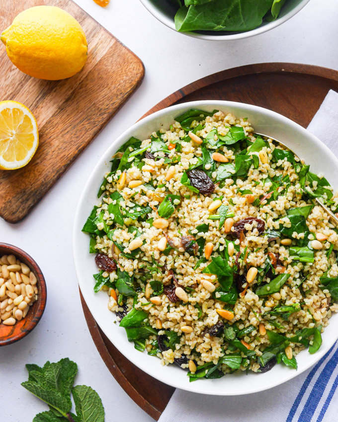 A bowl of bulgur salad resting on a wooden tray. Next to the bulgur and spinach salad is a chopping board with a cut lemon on it and a small bowl of pine nuts.