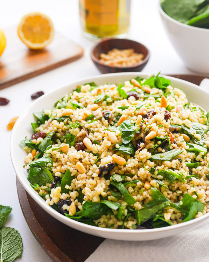 Bulgur Wheat Salad with Spinach, Pine Nuts & Raisins in a white bowl. The bowl is sitting on a wooden tray, and in the background you can see a bowl of pine nuts, raisins, and wedges of lemon.