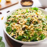 Bulgur Wheat Salad with Spinach, Pine Nuts & Raisins in a white bowl.