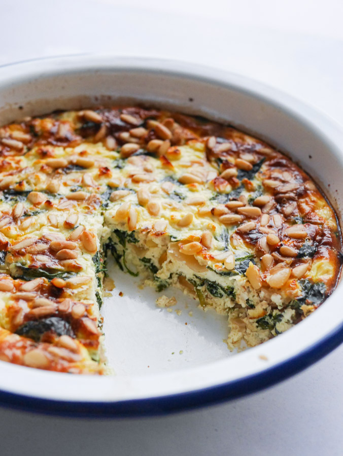 Spinach quiche with feta in a white enamel pie dish. A slice of the quiche has been removed.