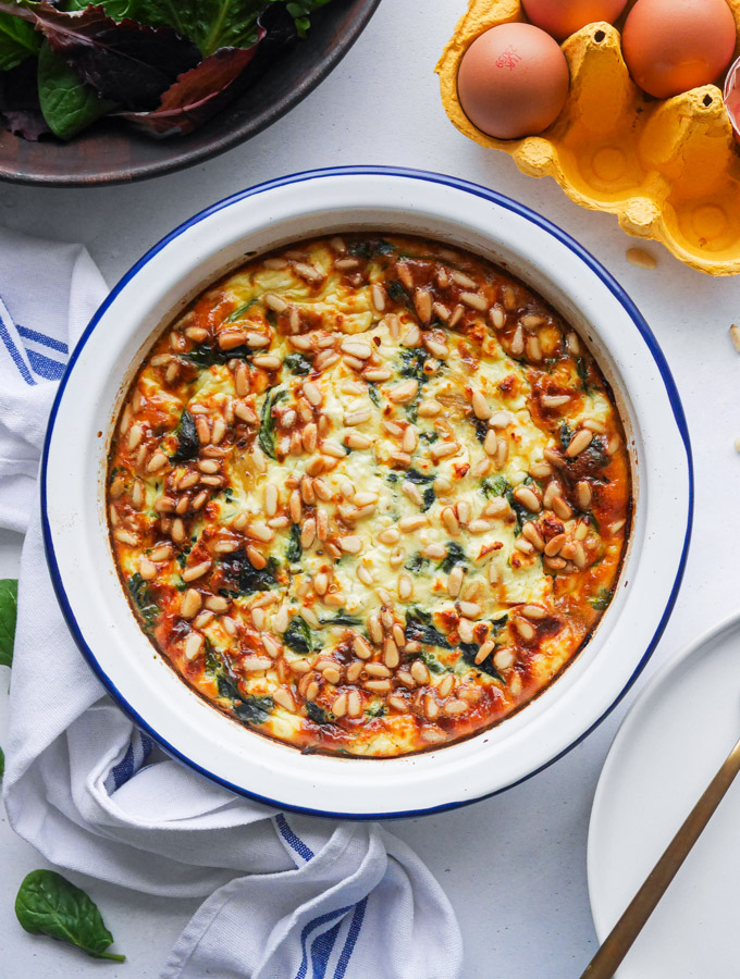 Spinach and feta quiche in a white enamel pie dish, topped with pine nuts, next to a bowl of salad leaves and a carton of eggs.
