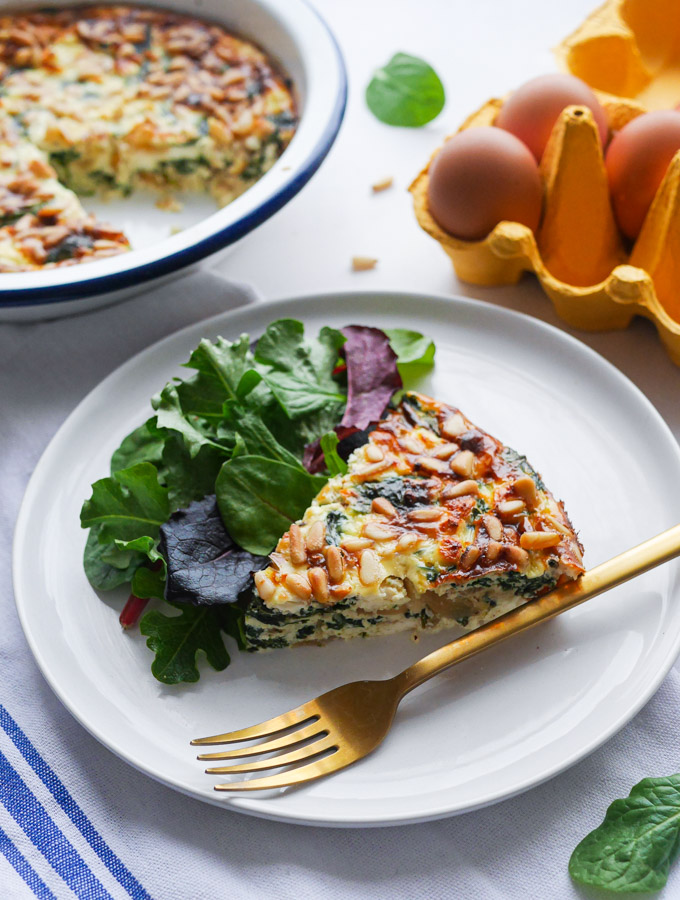 A slice of crustless spinach quiche on a plate served with salad. Next to the quiche is a gold fork.