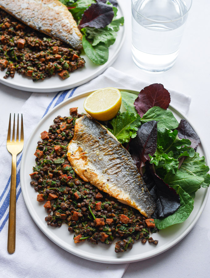 Sea Bass served with lentil and chorizo stew, a green salad and lemon wedge, on a white plate with a gold fork. Next to the plate is a glass of water and another plate of sea bass with chorizo & lentils.