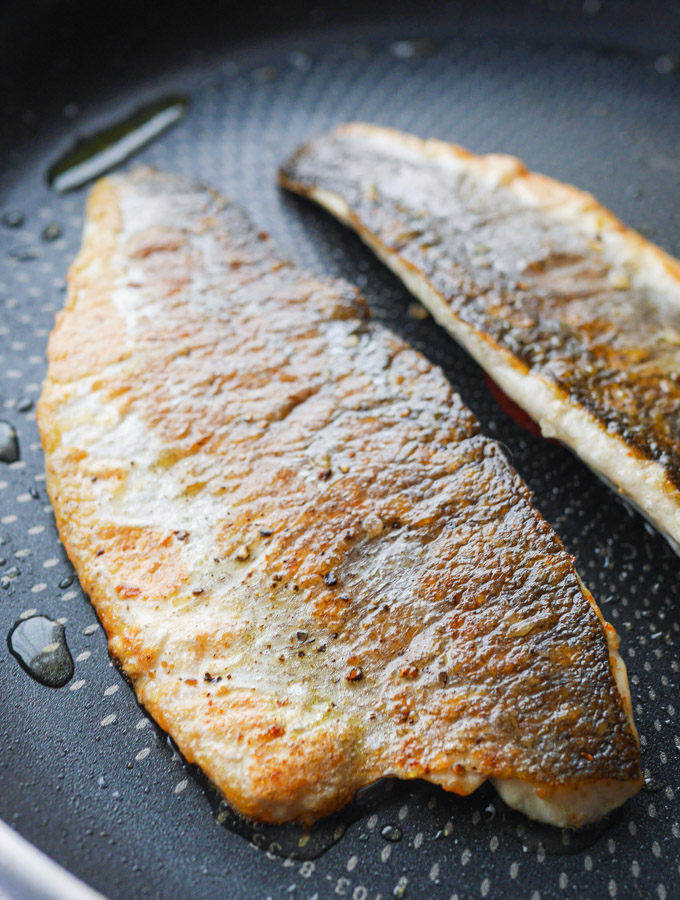 Two fillets of sea bass in a frying pan, skin side up, with crispy, golden brown skin.