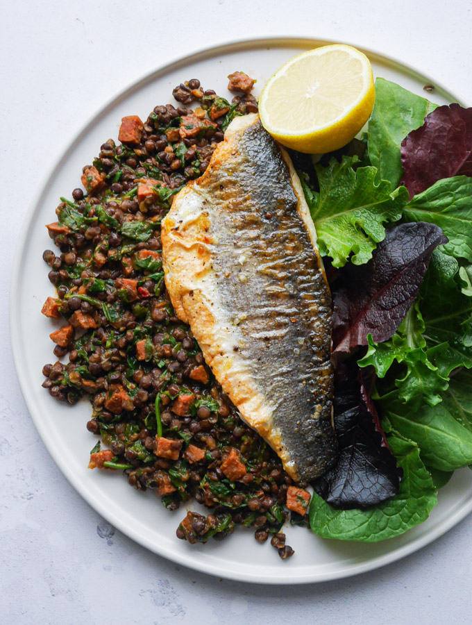 An overhead shot of pan-fried sea bass sitting on a bed of chorizo & lentils, served with a green salad and a wedge of lemon.