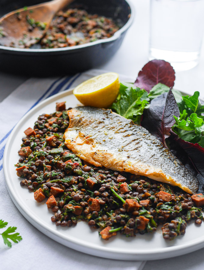Pan-fried sea bass sitting on a bed of chorizo & lentils, served with a green salad and a wedge of lemon. Next to the plate is a cast iron pan with more of the chorizo & lentil stew in.