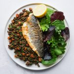 Pan-fried sea bass sitting on a bed of chorizo & lentils, served with a green salad and a wedge of lemon.